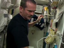 Commander Chris Hadfield performs<br /> maintenance on the Waste and Hygiene<br /> Compartment.<br /> Credit: NASA TV